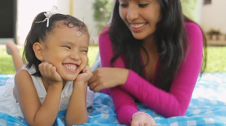 gün : Mom and Daughter Playful Behavior (HD). Hispanic mom & four year old girl playing and smiling on a blanket.