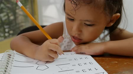muayene : Hispanic Girl With Math Homework (HD). Four year old Hispanic girl doing some math homework. Book pages are original custom made for the shoot so no copyright problems.  Stok Video