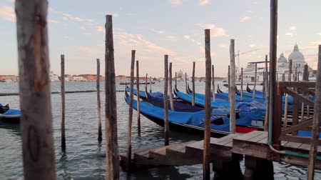 marcos : Venice Gondola Sunset (HD). Blue gondola boats docked near plaza Saint Marks Square in Venice Italy with far away view of San Giorgio Island. All logos and boat IDs removed or blurred out.