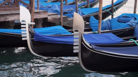 marcos : Venetian Gondolas Close Up (HD). Blue gondola boats close up view docked near plaza Saint Marks Square in Venice Italy with far away view of San Giorgio Island.