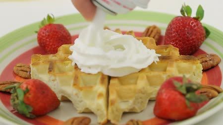 lét : Waffles With Whipped Cream. Strawberry pecan waffle dish with whipped cream being applied. Focus is in the waffle center. Stock mozgókép
