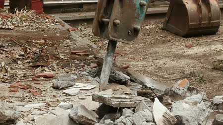 hidrolik : Loader Excavator Removing Debris (HD). Loader excavator arm loads concrete debris. Ambient audio included in two takes.