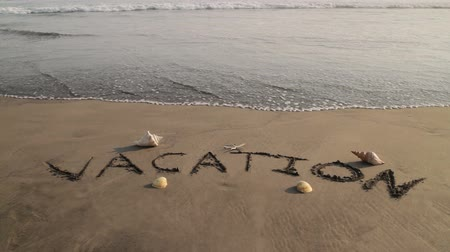 hvězdice : Vacation Sand Text Washed by Wave (HD). Vacation sign imprinted on sand with some sea shells on the sides and erased by a soft wave. Shot in Acapulco, Mexico. Dostupné videozáznamy