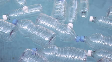 отходы : Plastic Bottles Floating On Water (HD). Plastic water bottles from different kinds floating on water.