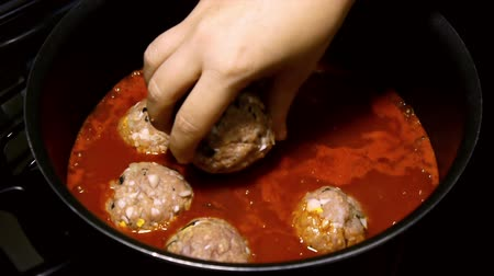 tomate : Beef Meatballs in Sauce Pot (HD). Beef Meatballs with onion, egg, peppermint and rice being placed for cooking in tomato sauce.