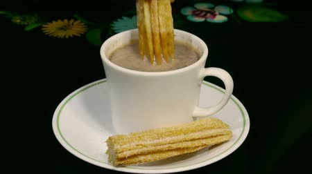 çikolata : Churros with Hot Cocoa (HD). Sweet fried churros with hot cocoa cup being dipped and eaten. Spanish and Mexican delicacy for dessert.