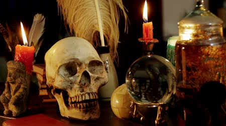 philosopher : Skull Witchcraft Desk Artifacts (HD). Occult study setup desk with a skull chandelier, candles, crystal ball, books, and other occult paraphernalia. Skull is resin replica not real. Stock Footage