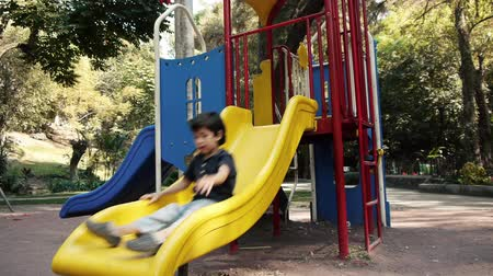 slayt : Kid Climbs and Slides on Playground Slide in Public Park.