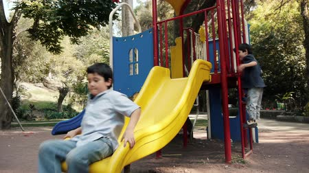 plac zabaw : Two Hispanic Latino Brothers Playing on a Public Park Slide.