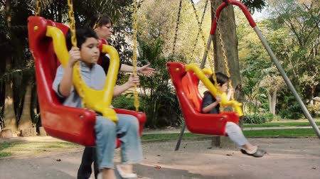 meksika : Mom Swinging Hispanic Kids on Swings at Public Park with Both Hands. Angle Five Stok Video