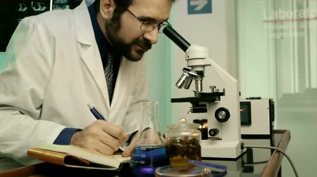 espécime : Male Scientist On Microscope (HD) Writes Findings while looking at sample.