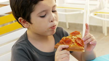 hladový : Boy Eating Pizza (HD). Six year old Hispanic boy eating a slice of pepperoni pizza.