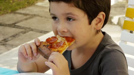 капелька : Kid with Acne Eats Pizza (HD). Six year old Hispanic boy eating a slice of pepperoni pizza with some acne on his face.