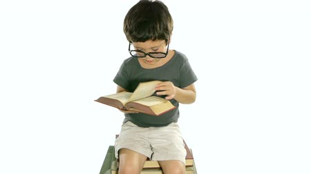 gramado : Boy Reading Book White Background (HD). Six year old boy with adult glasses; Hispanic origin flipping the pages of a book sitting on a pile of books over pure white illuminated background.