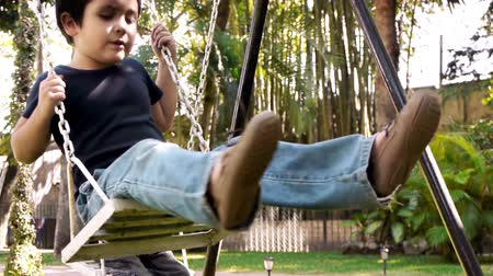 meksika : Brothers on Swing (HD). Two brothers of hispanic origin; six and four years old playing on a swing set. Seen from a three quarter angle. Stok Video