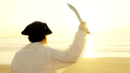 kalóz : Pirate Extending Short Dagger (HD). Pirate extends short sword dagger in two shot sequence while it lifts it at sunset.