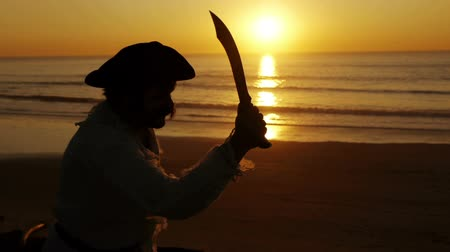 освещенный : Explorer With Dagger Silhouette (HD). Explorer or sailor silhouette against sunset with a dagger knife wielding it.