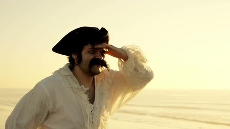 pirat : Pirate Looking At Ocean (HD). Pirate with white shirt looking at the Pacific Ocean horizon at sunset.