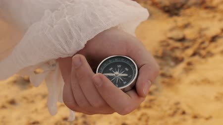 kalóz : Sailor With Compass (HD). Pirate sailor with white shirt looking his compass for direction near sundown on a sandy beach.