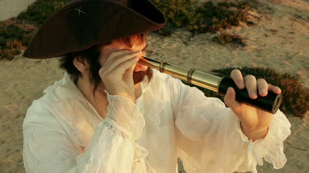 pirat : Pirate Holding Spyglass (HD). Pirate with white shirt looking at the horizon with an old fashioned spyglass at sunset.