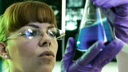 ученый : Female Scientist Looking at Flask (HD) looking and shaking a blue formula in a glass lab flask. Стоковые видеозаписи