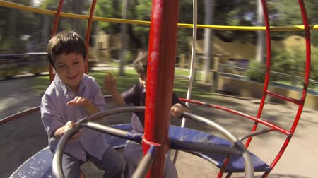 esferas : Hispanic Kid Brothers Play on Spinning Sphere at Public Playground. Inside View Stock Footage