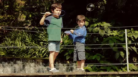 bubbels : Hispanic Kids blazen bubbels in Bridge over Water in het Park. Stockvideo