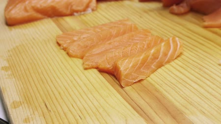 preparado : Placing Salmon Sashimi Cuts for sushi on wood board in rows. Stock Footage