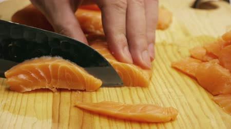 preparado : Pink Salmon Sashimi Cuts for sushi with Japanese Steel Knife on wood.