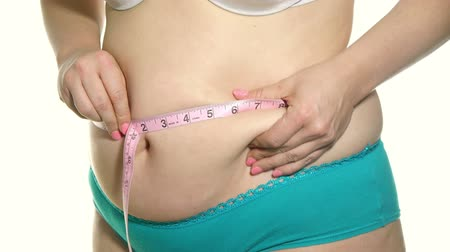 nadváha : Overweight Female Measuring Waist with Pink Measuring Tape. Massages fat afterwards.