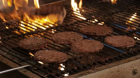 grelha : Close Up of Flipping Burgers In Metal Grill With Flames Shot in 4k