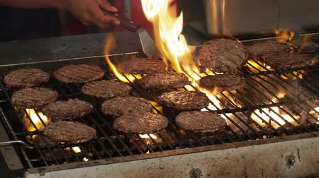 rook : Flipping hamburgers in Metal Grill Met Vlammen Schot in 4k Stockvideo