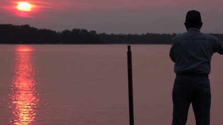 рыболовство : Senior man, fly-fishing (casting) off the end of a dock during a summer sunset. Footage shot off of Big Birch Lake in Minnesota, USA Стоковые видеозаписи