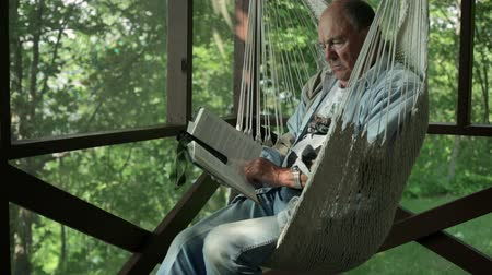 amadurecida : Senior man reading a book, while sitting in a hammock chair in a screen porch.