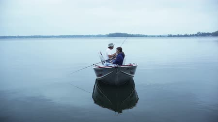 рыболовство : Mid-aged man and woman in a fishing boat, fishing together on an overcast day. Стоковые видеозаписи