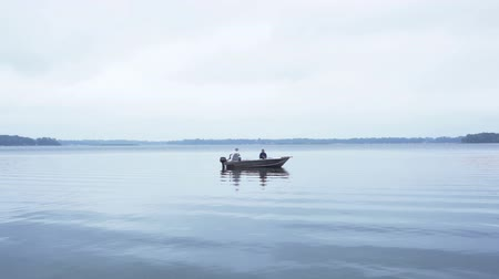 рыболовство : Midaged man and woman in a fishing boat, trolling and fishing together on an overcast day.