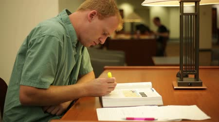 ödev : College student studying and doing homework inside a library on campus Stok Video