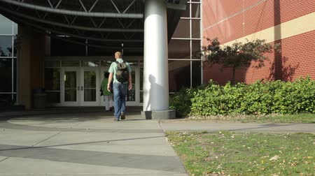 bina : College student walking on a university campus.