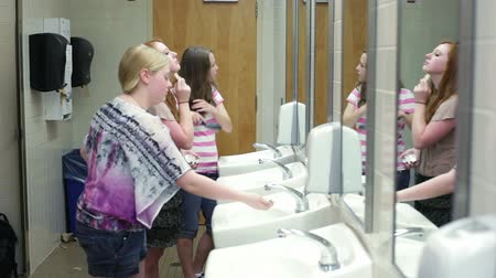 pletyka : A few girls (students) putting on makeup while talking in a school restroom