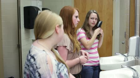 teatral : A few girls (students) putting on makeup while talking in a school restroom