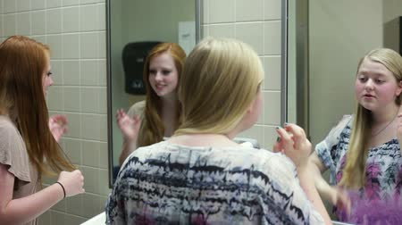 сплетни : A few girls (students) putting on makeup while talking in a school restroom