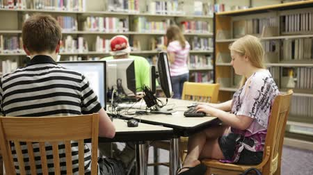 uczenie się : A group of students working & researching in the school library (media center) Wideo