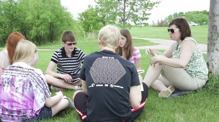 градация : High school teacher, teaching an informal class outside on a nice summer day