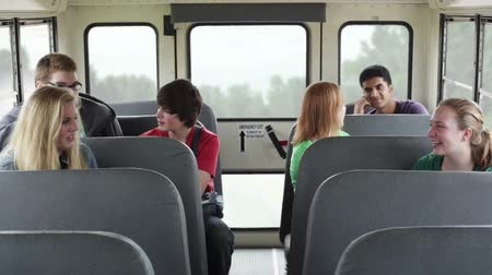 aluna : High school kids talking to each other while riding a school bus. Vídeos