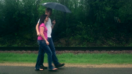 fırtına : Young couple (man and woman), playfully walking along a railroad track, under an umbrella in the rain. Stok Video