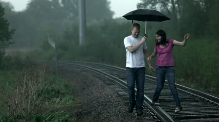 chuva : Young couple (man and woman), playfully walking along a railroad track, under an umbrella in the rain. Vídeos