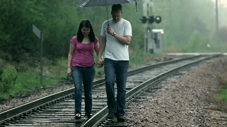 deszcz : Young couple (man and woman), playfully walking along a railroad track, under an umbrella in the rain. Wideo