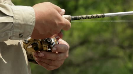 fenerbalığı : Mid-aged man and his father, fishing in a boat. Closeup on fishing reel and rod. Footage shot off of Big Birch Lake in Minnesota, USA