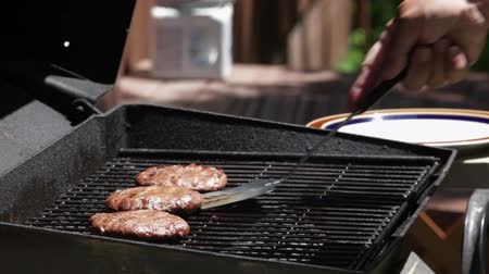 grilling : Mid-aged man, preparing hamburgers and hot dogs on a barbecue grill, outside a cabin on the lake.