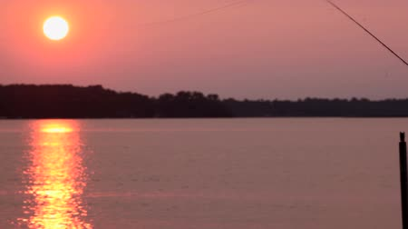 amadurecida : Senior man, fly-fishing (casting) off the end of a dock during a summer sunset. Footage shot off of Big Birch Lake in Minnesota, USA Stock Footage
